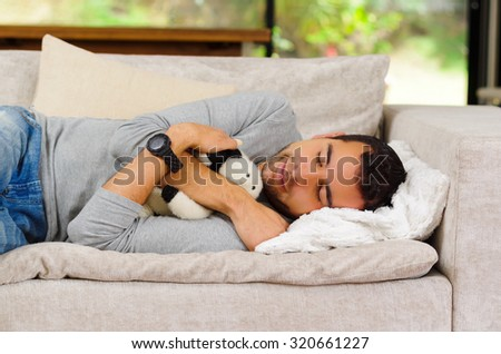 Hispanic male wearing blue sweater and jeans lying on white sofa with stuffed animal between arms sleeping. - stock photo