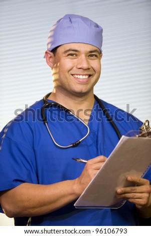 Hispanic male wearing scrubs with stethoscope around neck. - stock photo