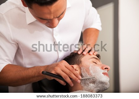 Hispanic man getting his beard shaved in a barber shop - stock photo