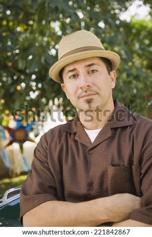 Hispanic man with arms crossed - stock photo