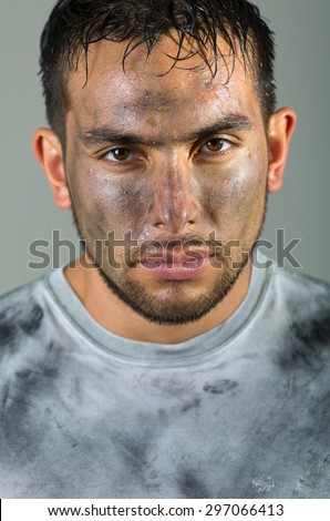 Hispanic man with dirty face and shirt looking to camera serious facial expression. - stock photo