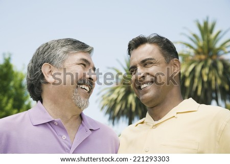 Hispanic men smiling at each other - stock photo