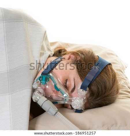 Hispanic middle age woman suffering form sleep apnea. Wearing cpap mask to relieve her condition or disorder - stock photo