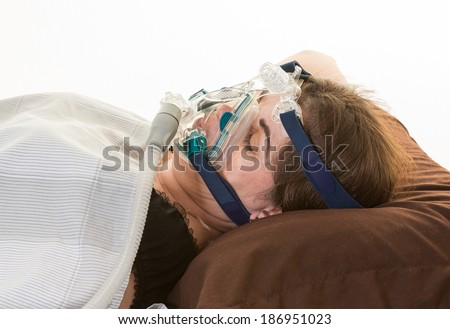 Hispanic middle age woman suffering from sleep apnea. Wearing a mask to relieve the condition - stock photo