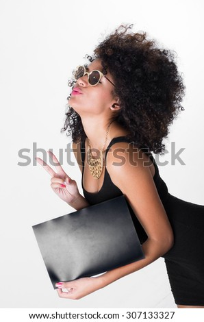 Hispanic model wearing black sexy dress and sunglasses holding blank board leaning forward making peace sign, shot from profile angle. - stock photo