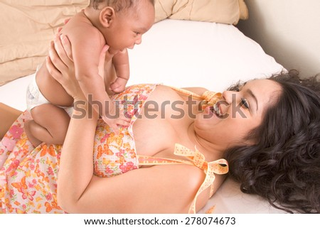 Hispanic mom lying down on bed and holding her biracial mix of Hispanic and African American infant son (baby is 7 weeks old) - stock photo