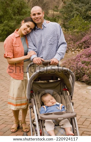 Hispanic parents with baby in stroller - stock photo