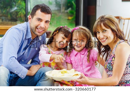 Hispanic parents with two daughters enjoying a tray of potato chips sitting in sofa while smiling and enjoying each other company. - stock photo