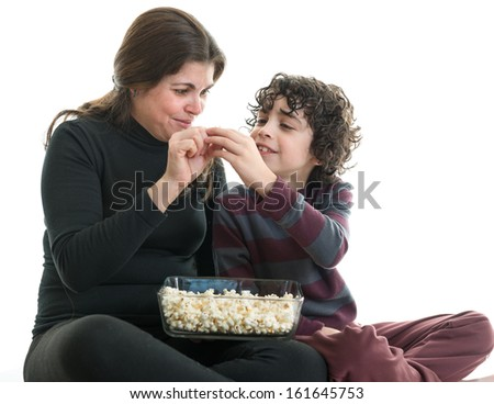 Hispanic single mother sharing popcorn with her eight years old son. Latin family enjoying the simplicity of life. White background. People isolated and in action - stock photo