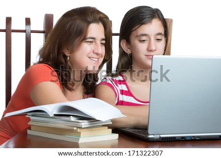 Hispanic teen and her mother working or browsing the web on a laptop computer isolated on white - stock photo