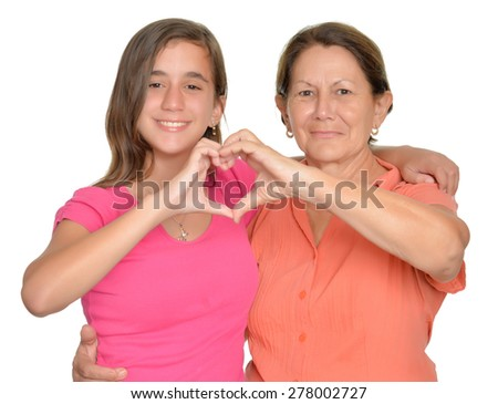 Hispanic teenage girl and her grandmother hugging and doing a heart sign with their hands - stock photo