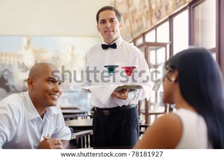 hispanic waiter serving adult couple at table in restaurant and looking at camera. Horizontal shape, front view, waist up - stock photo