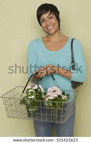 Hispanic woman carrying flowers in shopping basket - stock photo