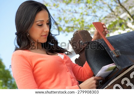 Hispanic Woman Checking Mailbox - stock photo