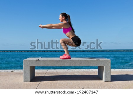 Hispanic woman doing squats on a bench by the ocean - stock photo