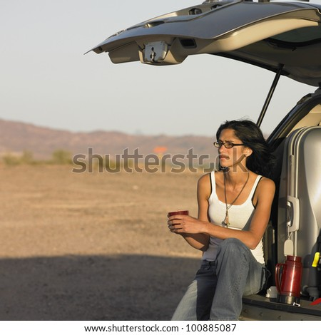 Hispanic woman in deserted area sitting on tailgate of truck - stock photo