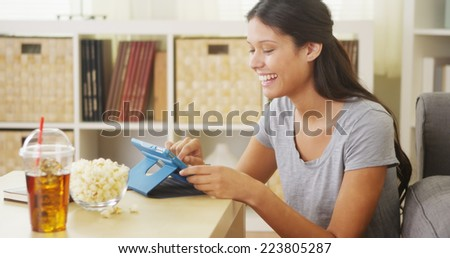 Hispanic woman laughing and using tablet on coffee table - stock photo