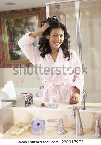 Hispanic woman looking in bathroom mirror - stock photo