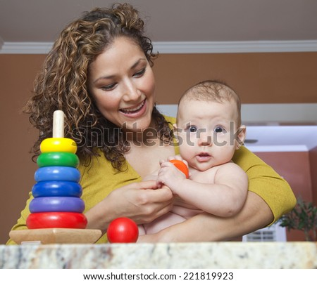 Hispanic woman playing with daughter - stock photo