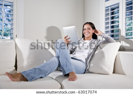Hispanic woman reading electronic book relaxing on couch - stock photo