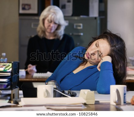 Hispanic woman sleeps at her office desk - stock photo