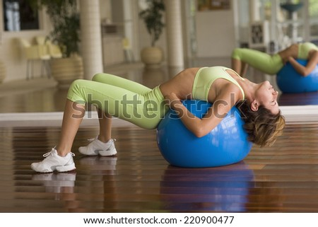 Hispanic woman stretching on exercise ball - stock photo