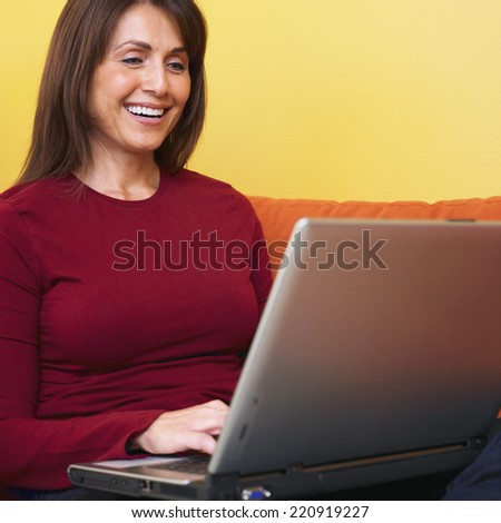 Hispanic woman typing on laptop - stock photo