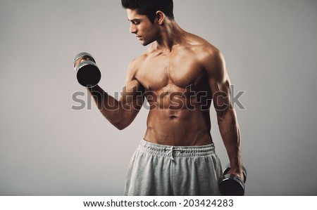 Hispanic young muscular man doing heavy dumbbell exercise for biceps. Fitness male model working out with dumbbells on grey background. - stock photo
