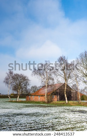 Historic agricultural barn in a rural landscape with snow. Abandoned agricultural barn in wintertime. - stock photo