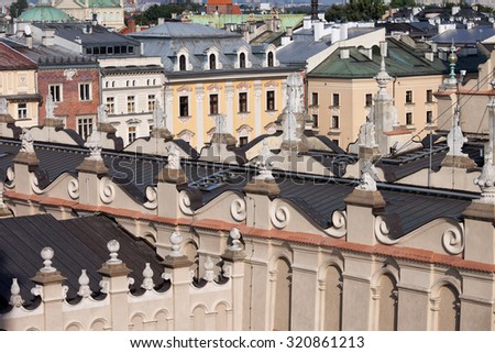 Historic architecture in the Old Town of Krakow in Poland. Decorative finials on rooftop of the Cloth Hall (Sukiennice) and old tenement houses. - stock photo