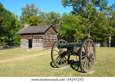 historic battlefield cabin and cannon - stock photo