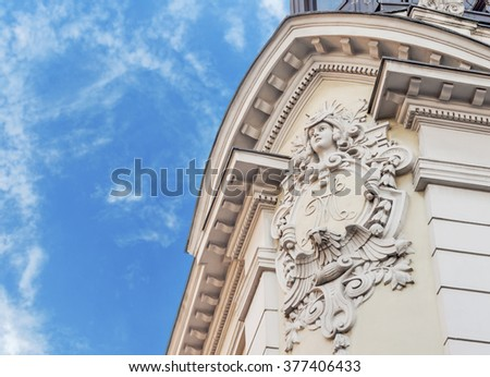 Historic building detail with blue cloudy sky - stock photo
