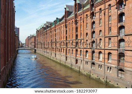 Historic canals among red brick storage facilities in the Speicherstadt harbor area of Hamburg, Germany. - stock photo