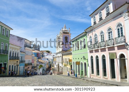 Historic city center of Pelourinho features brightly lit skyline of colonial architecture on a broad cobblestone hill in Salvador, Brazil  - stock photo