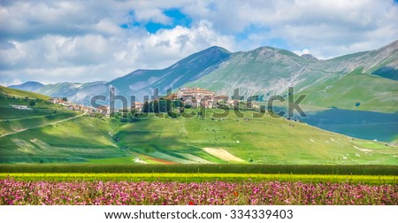 Historic city of Castelluccio di Norcia with beautiful summer landscape at Piano Grande (Great Plain) mountain plateau in the Apennine Mountains, Umbria, Italy - stock photo