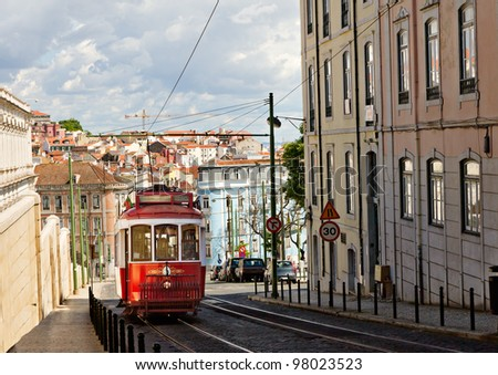 historic classic red tram of Lisbon built partially of wood navigating, narrow, winding streets, Portugal - stock photo