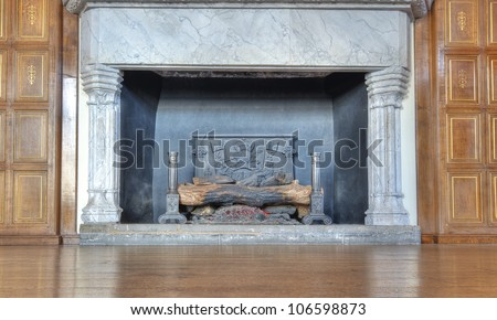 Historic fireplace with burning logs - stock photo