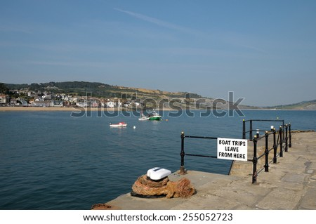 Historic harbour of Lyme Regis with coast view in Dorset - stock photo