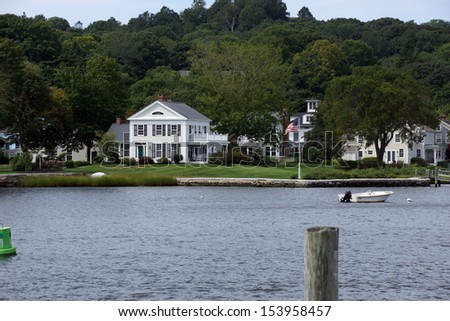 Historic New Enlgand mansions across the Thames river from wooden piers and wharfs, Old Mystic Seaport, Connecticut  - stock photo