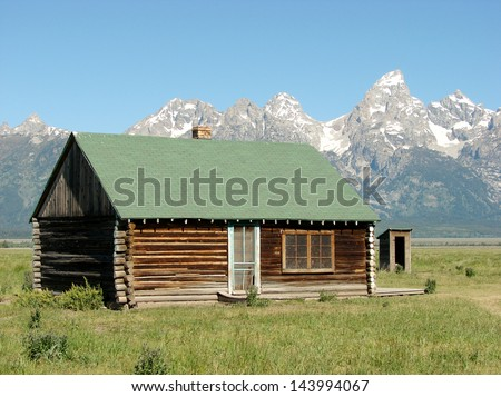 historic old farm buildings by mountains - stock photo