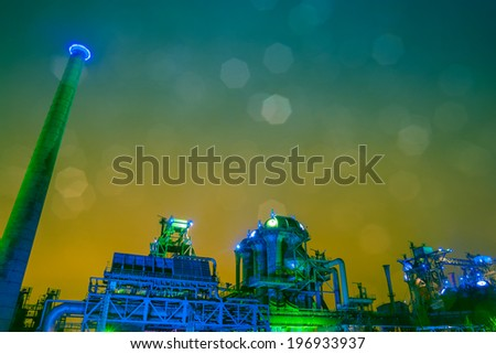 historic, old steel factory at night with illuminated color lighting, from green to blue, and real bokeh shapes - stock photo