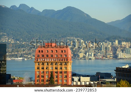 Historic Second Empire style Dominion Building and North Vancouver city skyline across Vancouver Harbour, Vancouver, British Columbia, Canada. - stock photo