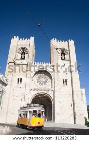 Historic yellow tram in front of Se Cathedral in Lisbon, Portugal - stock photo