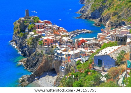Historical buildings and distant fortress above the sea in Vernazza, Cinque Terre, Italy - stock photo
