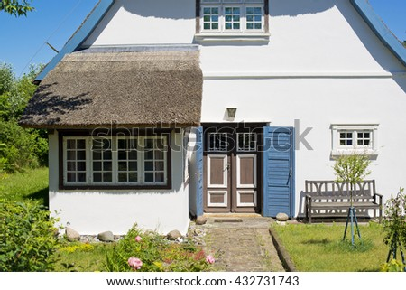 historical house with thatched roof and blue sky at the German Baltic Sea coast, Germany, Europe - stock photo