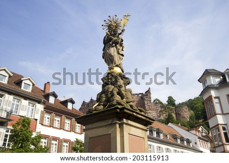 Historical monument on a town square in old Heidelberg, Germany, with the ruins of the castle on the hill in the background - stock photo