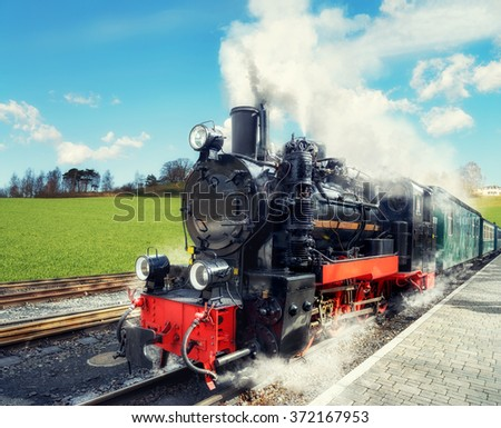 Historical steam train on island Rugen in Nothern Germany on a bright day in Spring. This image is toned. - stock photo