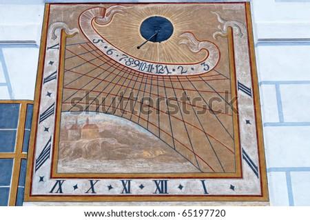 Historical sundial or sun clock on a wall in Cesky Krumlov. - stock photo