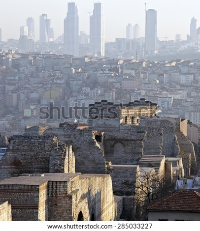 History meets nowadays. Ancient ruins of Theodora Byzantine Wall in Istanbul and modern skyline of buildings on background at soft sunrise - stock photo