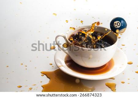 Hit billiard ball into coffee cup - stock photo